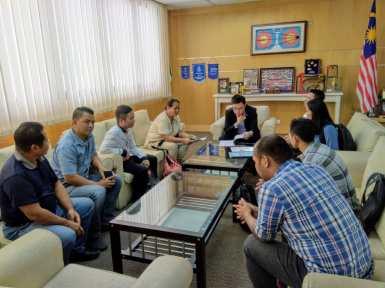 YB Ginger Phong Jie Zie sedang berbincang dan meneliti dokumen dari pihak rombongan.